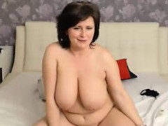 Voluptuous housewife Celine lies on the bed and pleases her